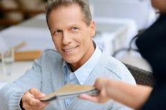 Hombre agradable que se sienta en la tabla Imagen de archivo libre de regalías