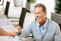 Hombre agradable que se sienta en la tabla Fotos de archivo libres de regalías