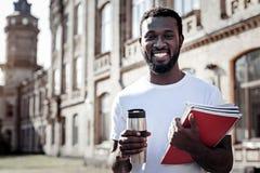 Hombre alegre agradable que sostiene una taza terma fotos de archivo libres de regalías