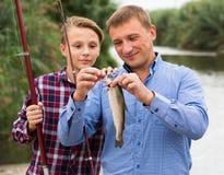 Hombre alegre con el hijo que mira pescados en el gancho Foto de archivo