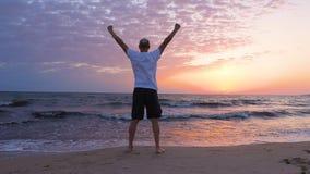 Hombre alegre con el levantamiento encima de las manos que saluda puesta del sol de la mañana en la playa del mar almacen de metraje de vídeo