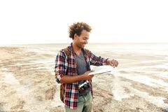 Hombre alegre con la situación de la mochila y el mapa examening al aire libre Imagen de archivo