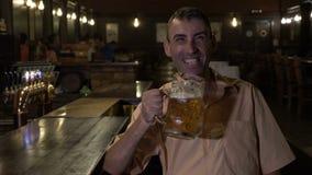 Hombre alegre de risa que come una cerveza y que ve la TV en la barra - almacen de video
