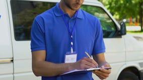Hombre alegre del servicio de entrega que completa la declaración y que muestra los pulgares-para arriba almacen de video