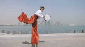 Hombre alegre en el baile ucraniano del traje en los zancos con los tambores al aire libre en el slo-MES almacen de metraje de vídeo