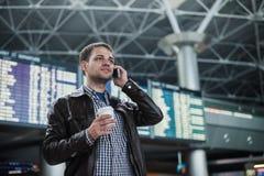 Hombre alegre en el teléfono móvil en la estación del pasillo delante de horario del tablero Imágenes de archivo libres de regalías