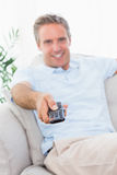 Hombre alegre en su sofá que ve la TV Imagen de archivo