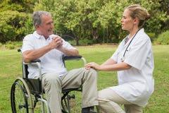 Hombre alegre en una silla de ruedas que habla con su enfermera que se arrodilla por otra parte Foto de archivo libre de regalías