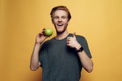 Hombre alegre feliz que detiene la manzana y los pulgares verdes foto de archivo libre de regalías