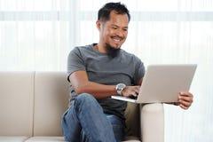 Hombre alegre filipino con el ordenador portátil imagen de archivo