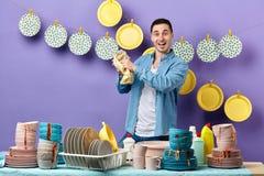 Hombre alegre hermoso que limpia la placa con la toalla en la cocina imagen de archivo libre de regalías