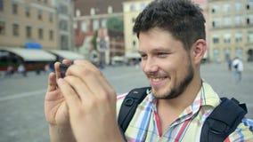Hombre alegre hermoso que toma la foto con el teléfono móvil en Wroclaw, Polonia almacen de metraje de vídeo