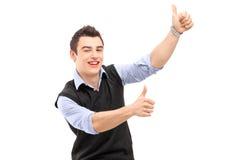 Hombre alegre joven que gesticula felicidad con los pulgares para arriba Fotos de archivo libres de regalías