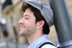Hombre alegre joven que se inclina en la lámpara de calle Fotos de archivo libres de regalías