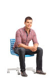 Hombre alegre joven que se sienta en una silla foto de archivo