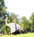 Hombre alegre joven que sostiene una bola y que gesticula felicidad en Imagen de archivo libre de regalías