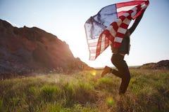 Hombre alegre que corre con la bandera de los E.E.U.U. Fotografía de archivo