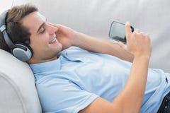 Hombre alegre que disfruta de música con su smartphone Imagen de archivo