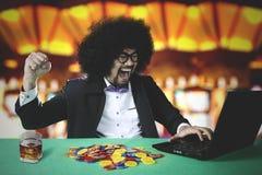 Hombre alegre que gana el póker en línea en casino imagenes de archivo