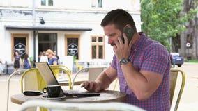 Hombre alegre que juega al juego en la tableta en café almacen de video
