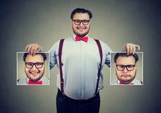 Hombre alegre que muestra diversas fotos con emociones imagen de archivo