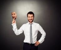 Hombre alegre que oculta detrás de máscara enojada Fotos de archivo libres de regalías
