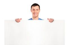 Hombre alegre que se coloca detrás de un panel en blanco Imagenes de archivo