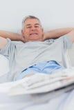 Hombre alegre que se relaja en cama Fotos de archivo