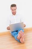 Hombre alegre que se sienta en el piso usando el ordenador portátil Imágenes de archivo libres de regalías