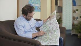 Hombre alegre que se sienta en el sofá y que elige a la ciudad de vacaciones en el mapa, aventurero almacen de video
