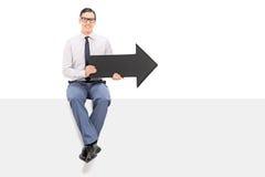 Hombre alegre que se sienta en un panel y que sostiene una flecha Imágenes de archivo libres de regalías