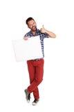 Hombre alegre que sostiene el cartel en blanco y que muestra los pulgares para arriba Foto de archivo libre de regalías