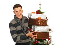 Hombre alegre que sostiene los regalos de la Navidad Fotos de archivo