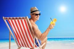 Hombre alegre que sostiene un cóctel en una playa Foto de archivo libre de regalías