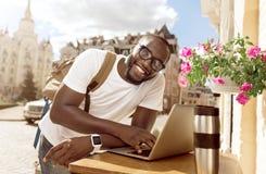 Hombre alegre que usa el ordenador portátil foto de archivo libre de regalías
