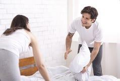 Hombre alegre y mujer que hacen la cama junto fotos de archivo