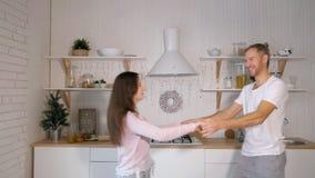 Hombre alegre y mujer sonrientes que se divierten en la sala de estar moderna acogedora, el marido feliz y la esposa disfrutando  almacen de metraje de vídeo