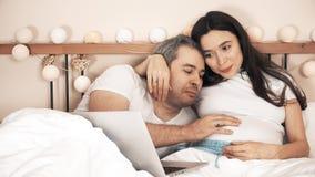 Hombre alegre y su esposa embarazada que usa su ordenador portátil en cama en casa almacen de metraje de vídeo