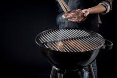 Hombre alrededor para colocar la carne cruda en un fuego caliente del Bbq Fotografía de archivo
