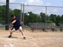 Hombre alrededor para golpear un beísbol con pelota blanda Imágenes de archivo libres de regalías