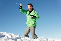 Hombre alrededor para lanzar la bola de nieve Fotos de archivo libres de regalías