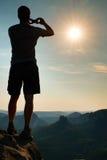 Hombre alto en negro en el acantilado con el arbusto del brezo Parque agudo de las montañas rocosas Imagen de archivo libre de regalías