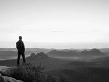 Hombre alto en negro en el acantilado con el arbusto del brezo Parque agudo de las montañas rocosas Imágenes de archivo libres de regalías
