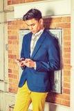 Hombre americano asiático joven que manda un SMS en el teléfono celular afuera en nuevo Yo Imagen de archivo libre de regalías