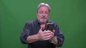 Hombre americano cabelludo gris mayor que habla en videochat en el tel?fono aislado en fondo verde del chromakey metrajes