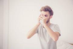 hombre americano con la taza de café en dormitorio con mañana Imagen de archivo libre de regalías