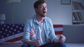 Hombre americano emocional que agita la bandera de los E.E.U.U. y que mira resultados de elección en hogar de la TV almacen de video