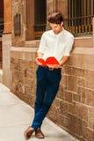 Hombre americano joven que lee el libro rojo afuera en Nueva York Foto de archivo