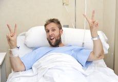 Hombre americano joven que miente en cama en el sitio de hospital enfermo o enfermo pero que hace la muestra de la victoria con l Imagen de archivo