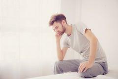 Hombre americano que bosteza El hombre que sienta una cama es serio y problema Foto de archivo libre de regalías